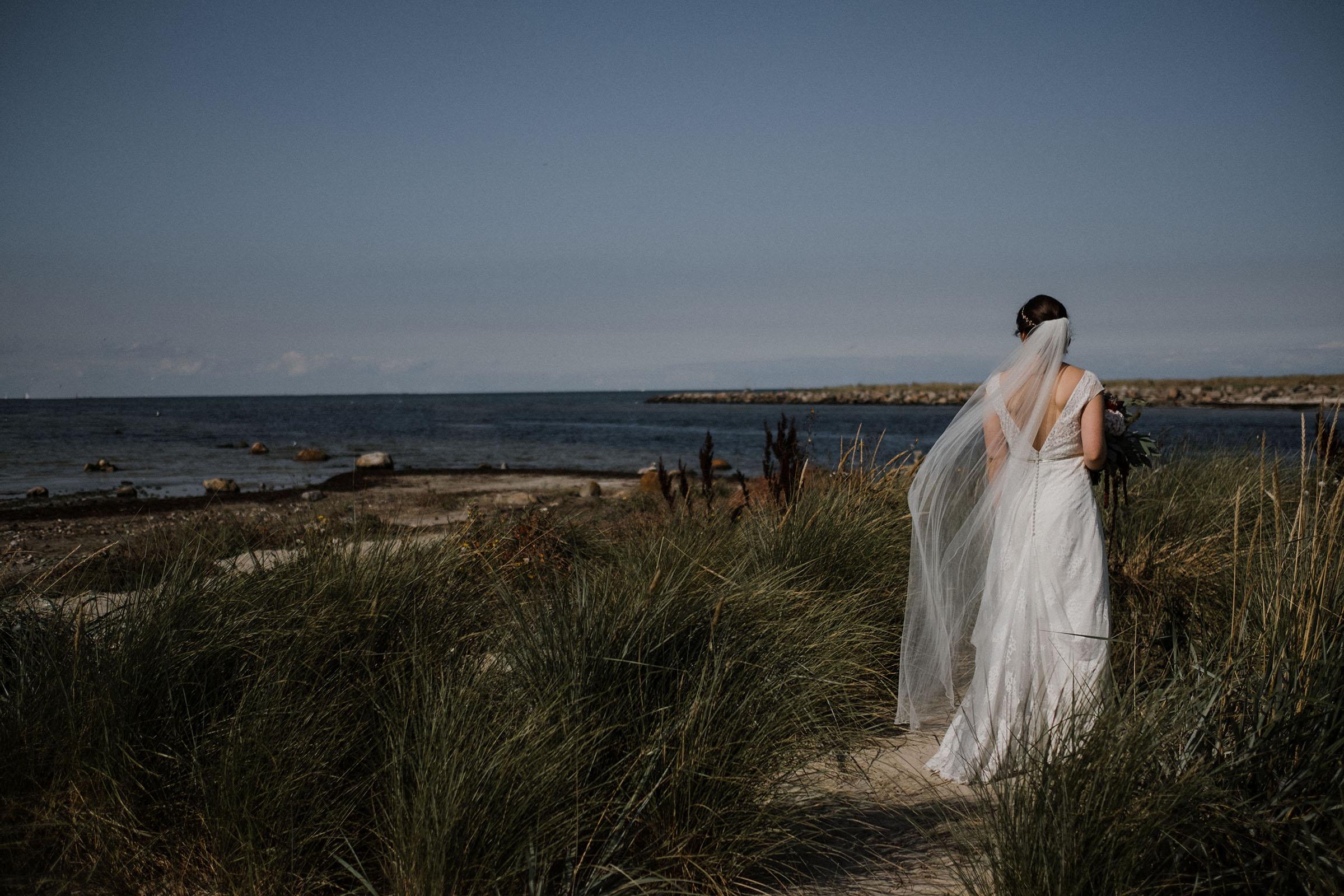 Hochzeitsfotografie in Kiel_Frau-Siemers_Falkensteiin_Portraitaufnahme des Brautpaares_Rückenaufnamhe der Braut, die aufs Meer blickt.