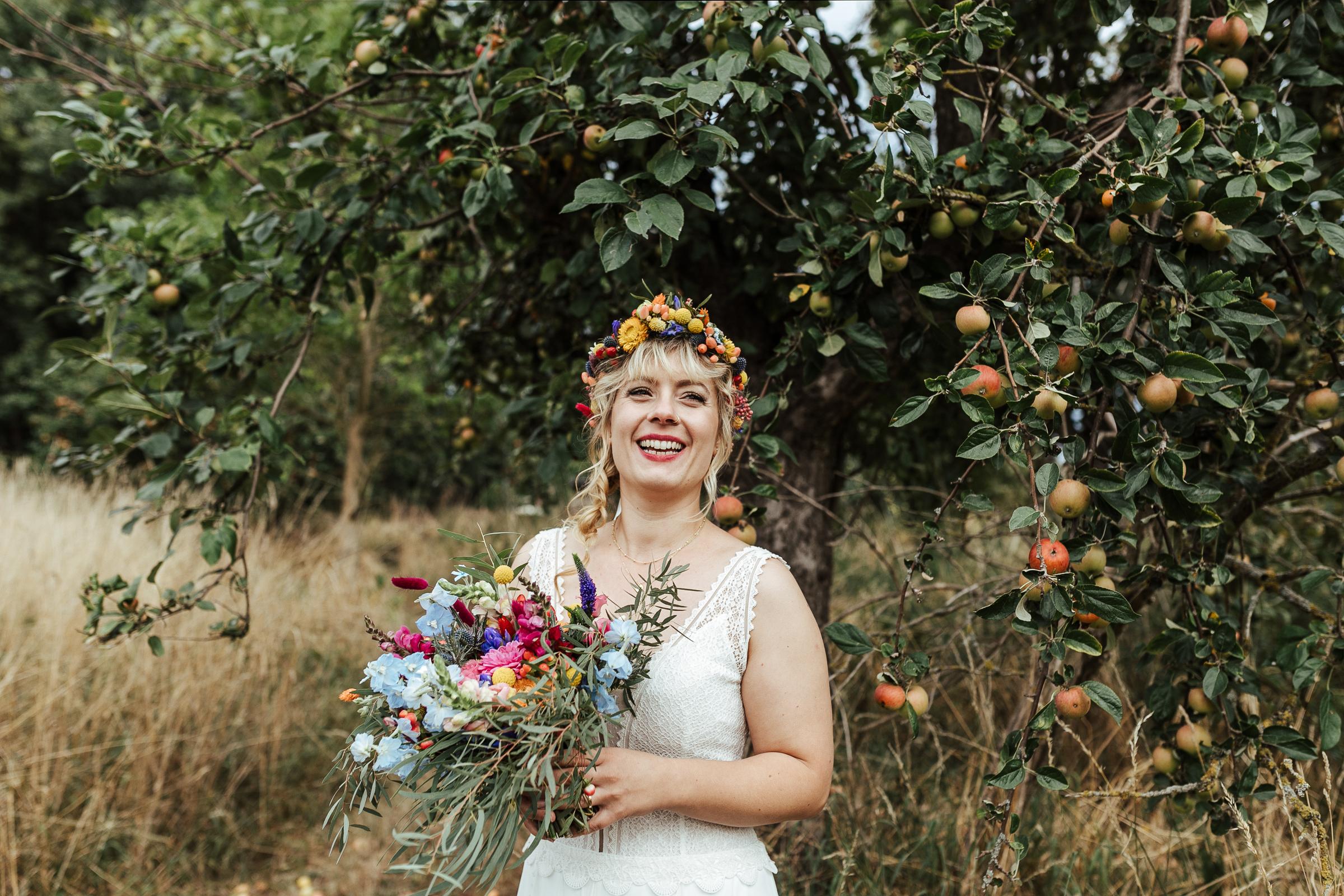 lachende Braut mit Blumenkranz im Haar und Brautstrauß