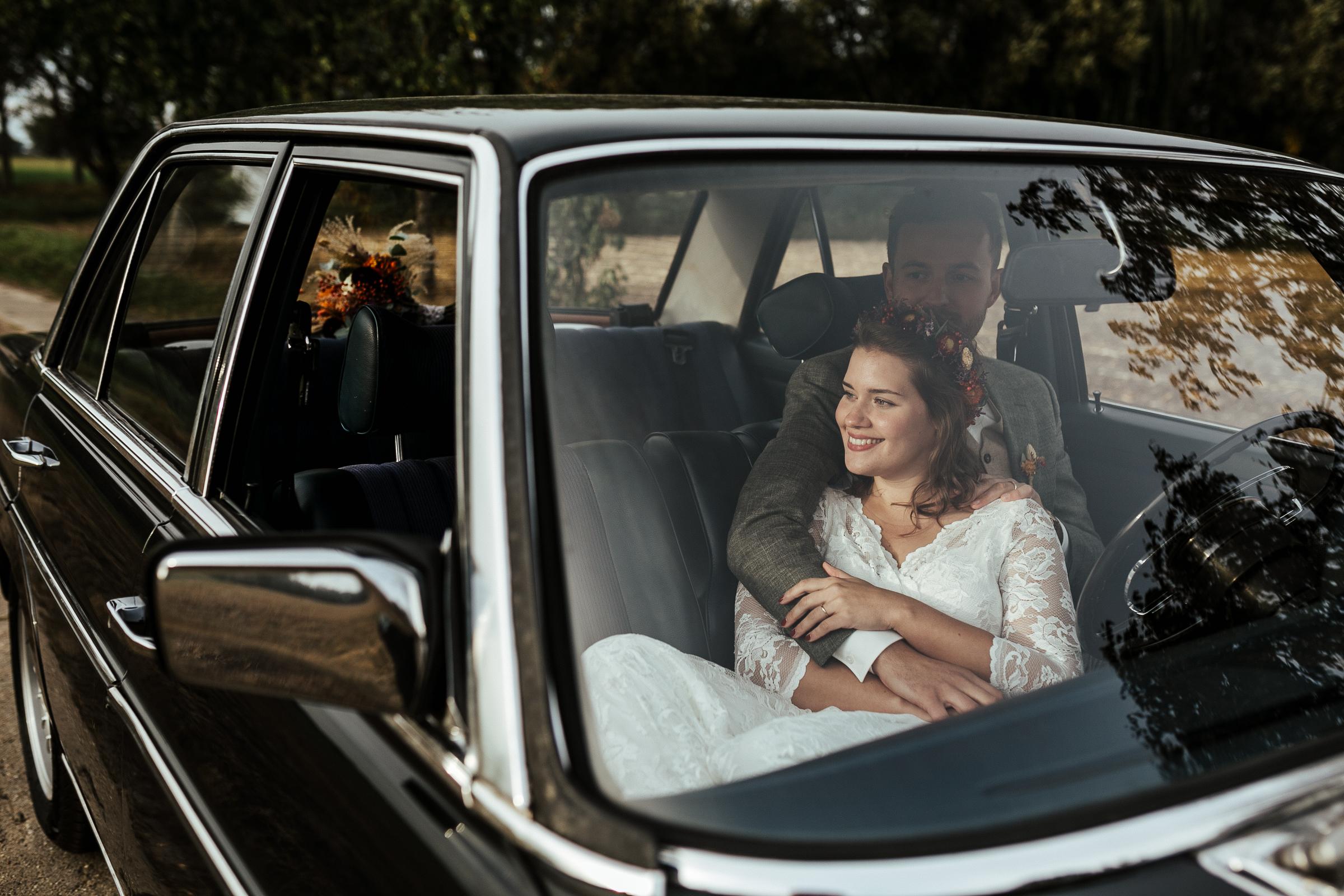 Blumenschmuck von Kopflegenden: Brautpaar im Auto