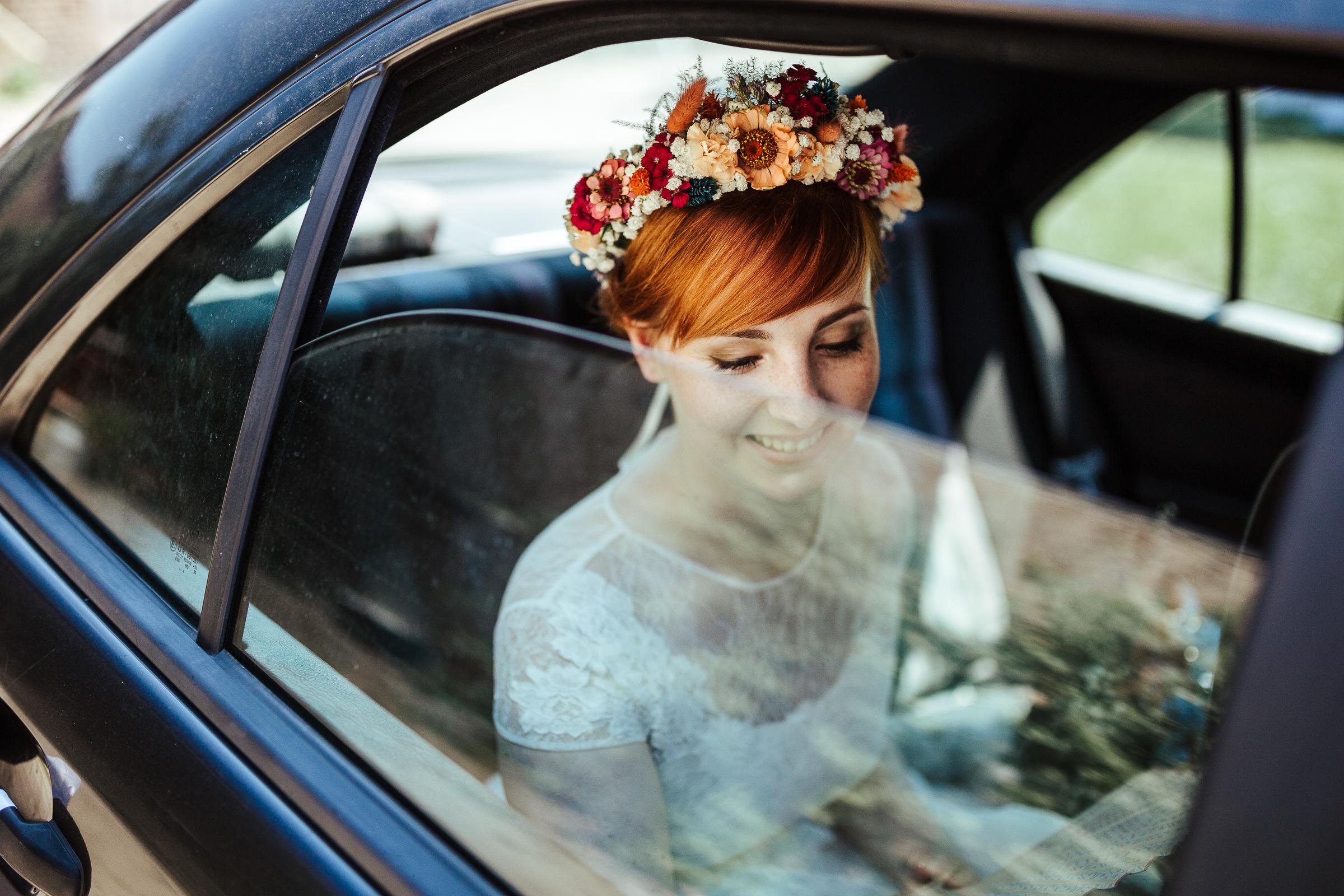 Blumenschmuck von Kopflegenden: Braut mit Blumekranz im Auto