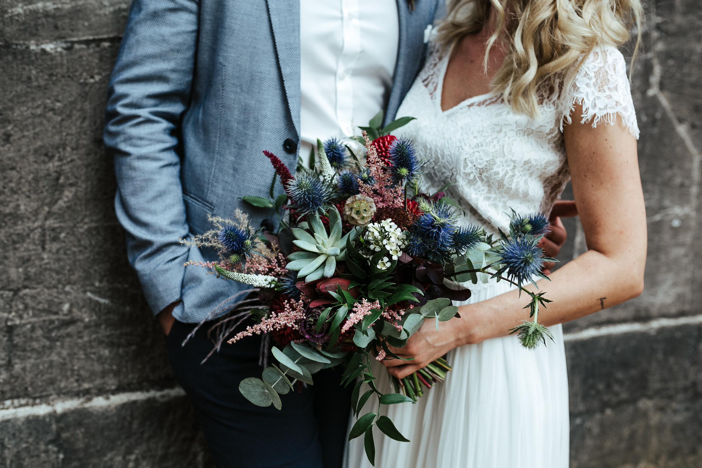 Blumenschmuck von Kopflegenden: Brautpaar mit Brautstrauß